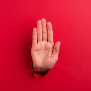 "hand braking through red background to show ""stop"""