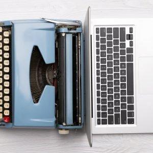 Classic analog typewriter vs Modern digital hi-tech laptop computer